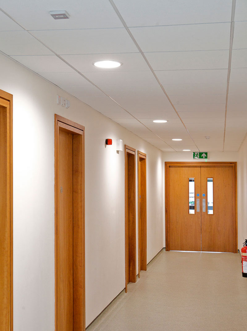 ROBUS INSPIRE Activate LED Downlights and ROBUS Emergency Exit Box installed in one of the corridors in Takeda Ireland, Grange Castle