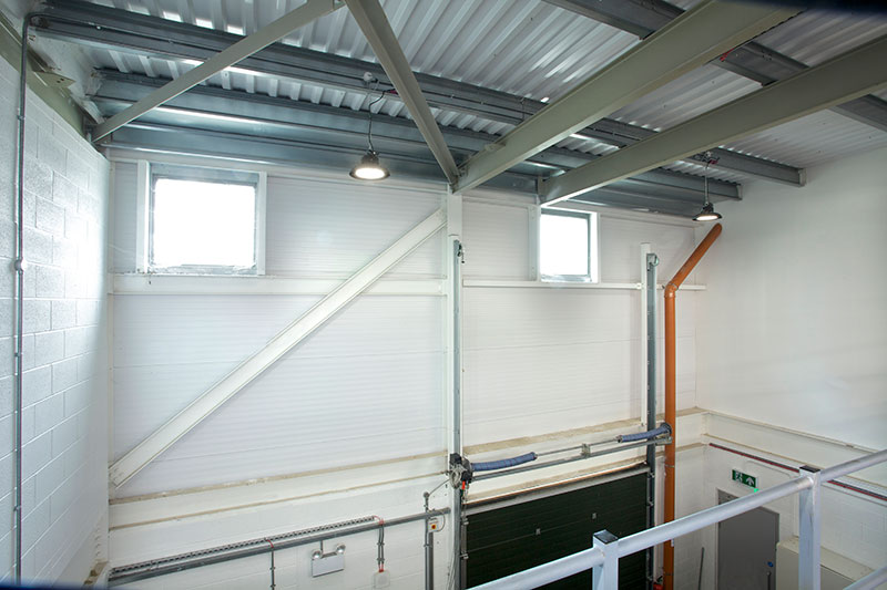 ROBUS SONIC LED High Bay installed in the double height ceiling over the workshop shutter door in Takeda Ireland, Grange Castle